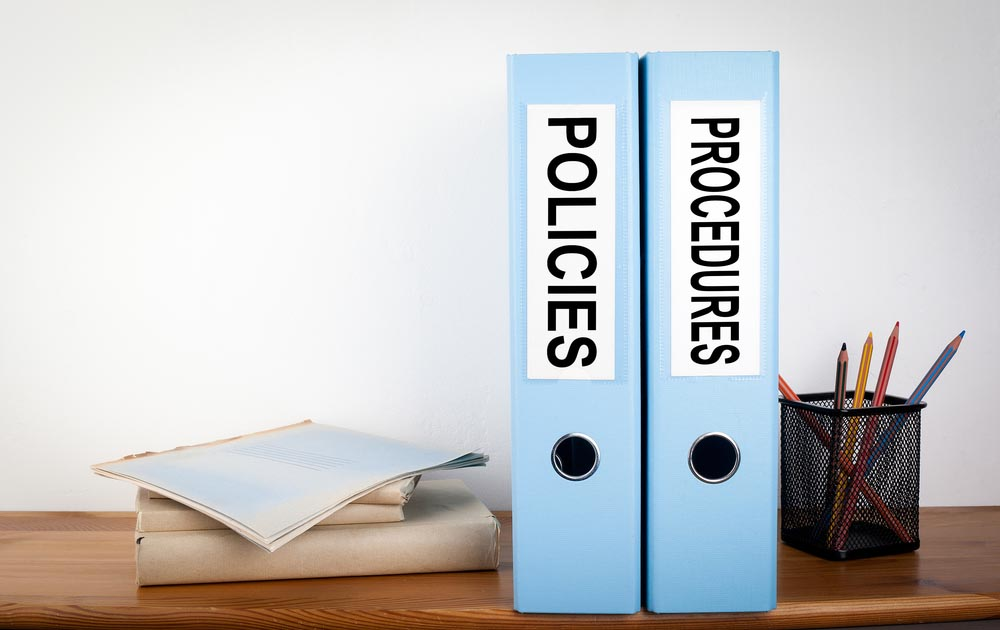 Picture of two folder binders with the words Policies and Procedures on the spine placed next to expense reports
