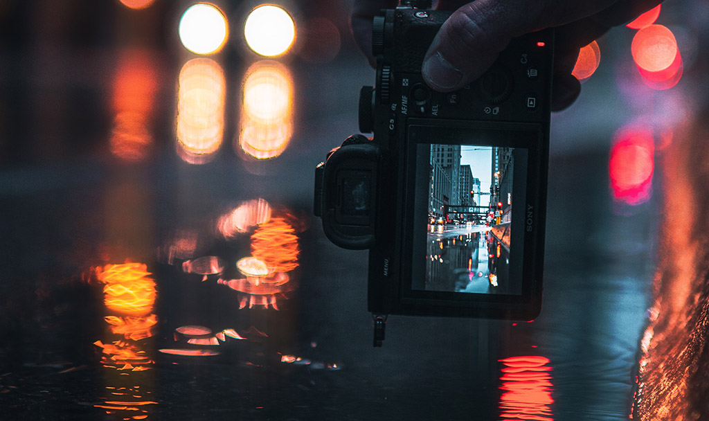 Street photographer taking a picture of a rain soaked street in a city