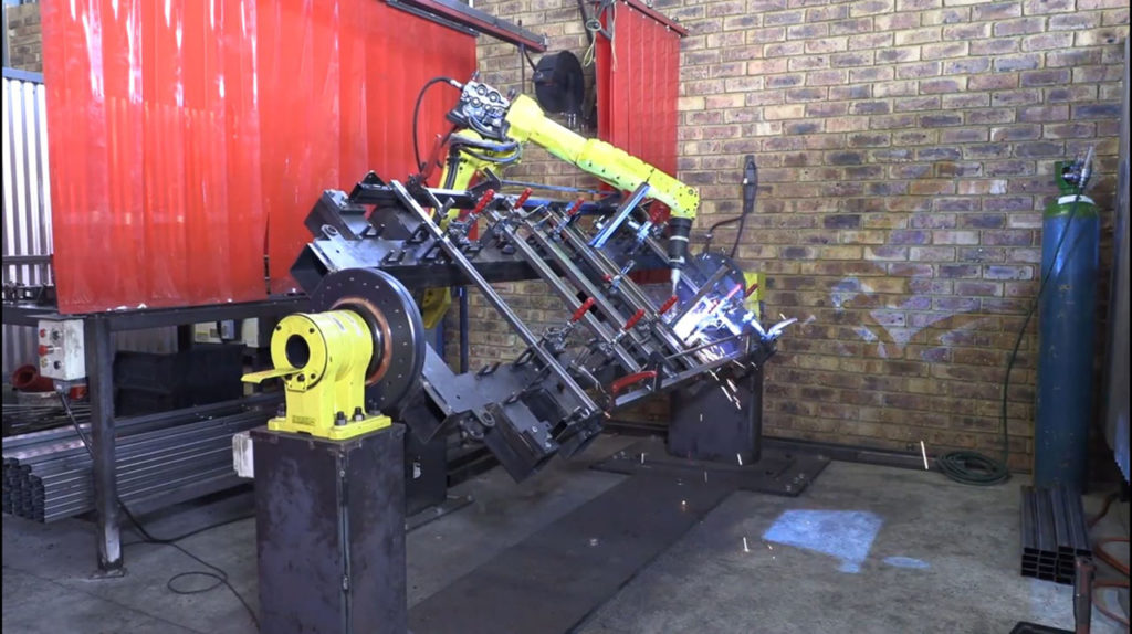 Robotic welding arm welding a jig in the Hospi-Furn company profile film