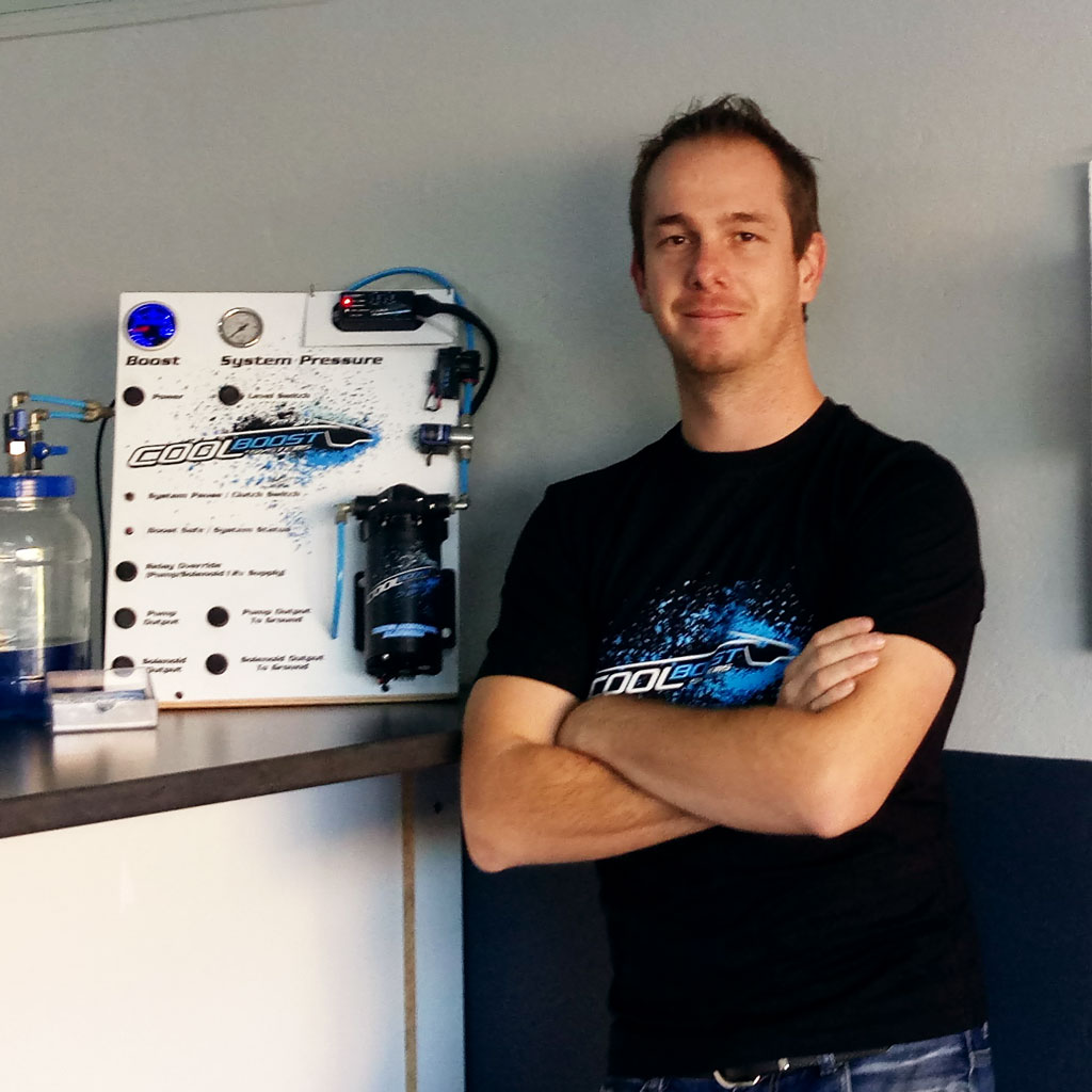 Brendan Penny, the founder of Cool Boost Systems standing next to a water methanol injection display