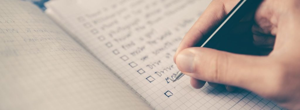 Man who is about to start marketing by writing down objectives in a notebook with a black pen